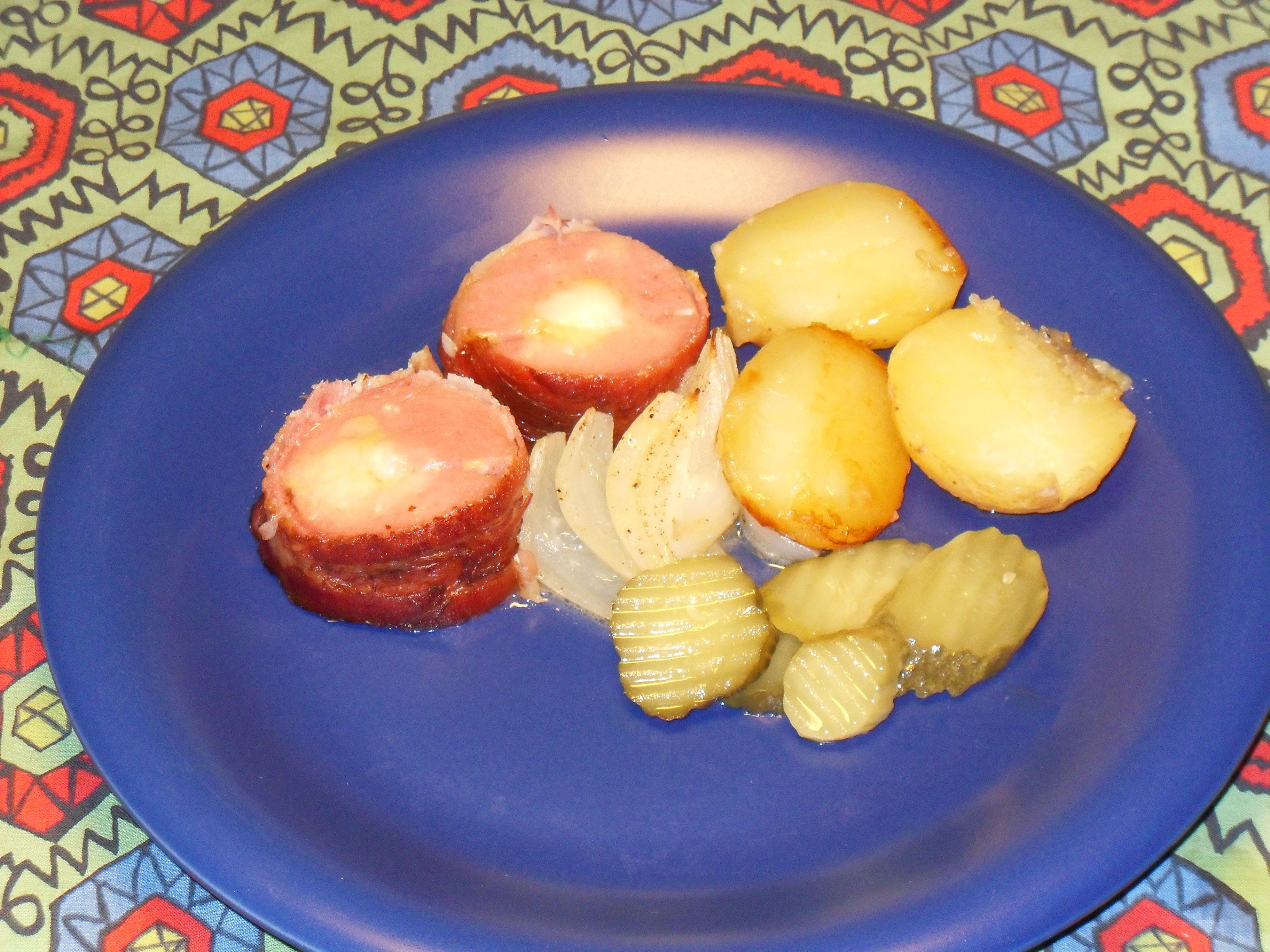 Briespäckad baconfalukorv på potatisbädd