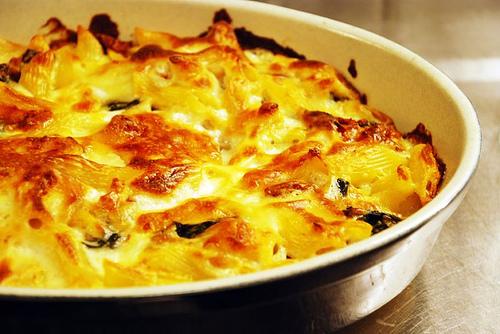 Potatisgratäng med soltorkade tomater, feta och spenat
