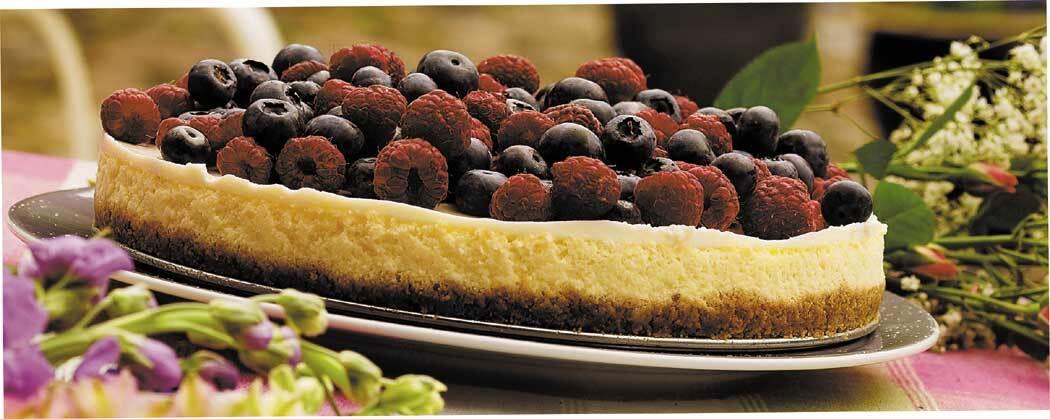 Cheesecake garnerad med hallon och blåbär
