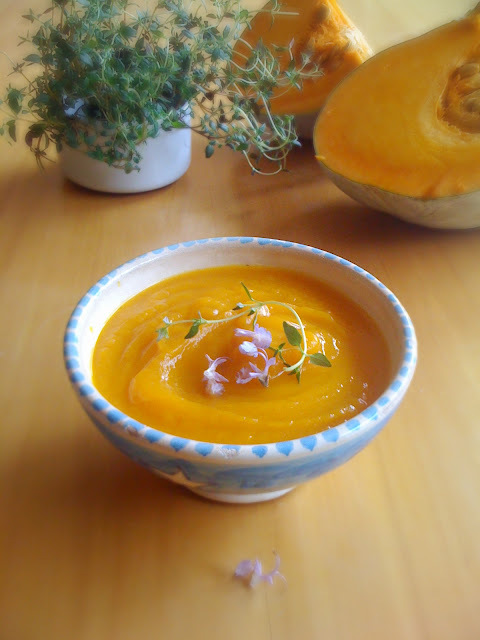 Pumpkin and red onion soup with thyme and rosemary flowers