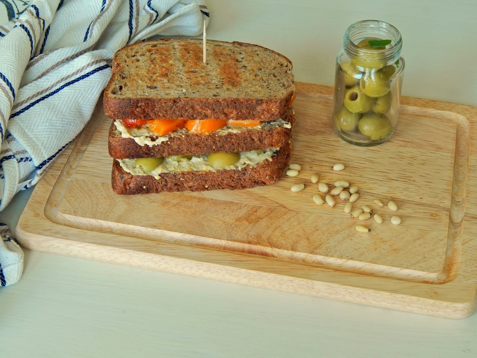 Toasted houmous, roast pepper, olive and pine nut sandwich