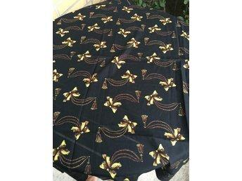 Sjal mönster av guld o brunt på svart botten.