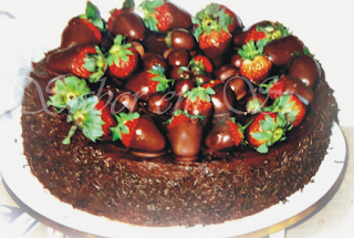 de bolo de chocolate bem molhadinho e com recheio branco e cobertura de morangos e chocolate