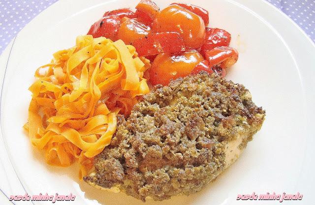 Peito de frango com crosta de pesto acompanhado por talharim de cenoura com pimentões e tomates grelhados