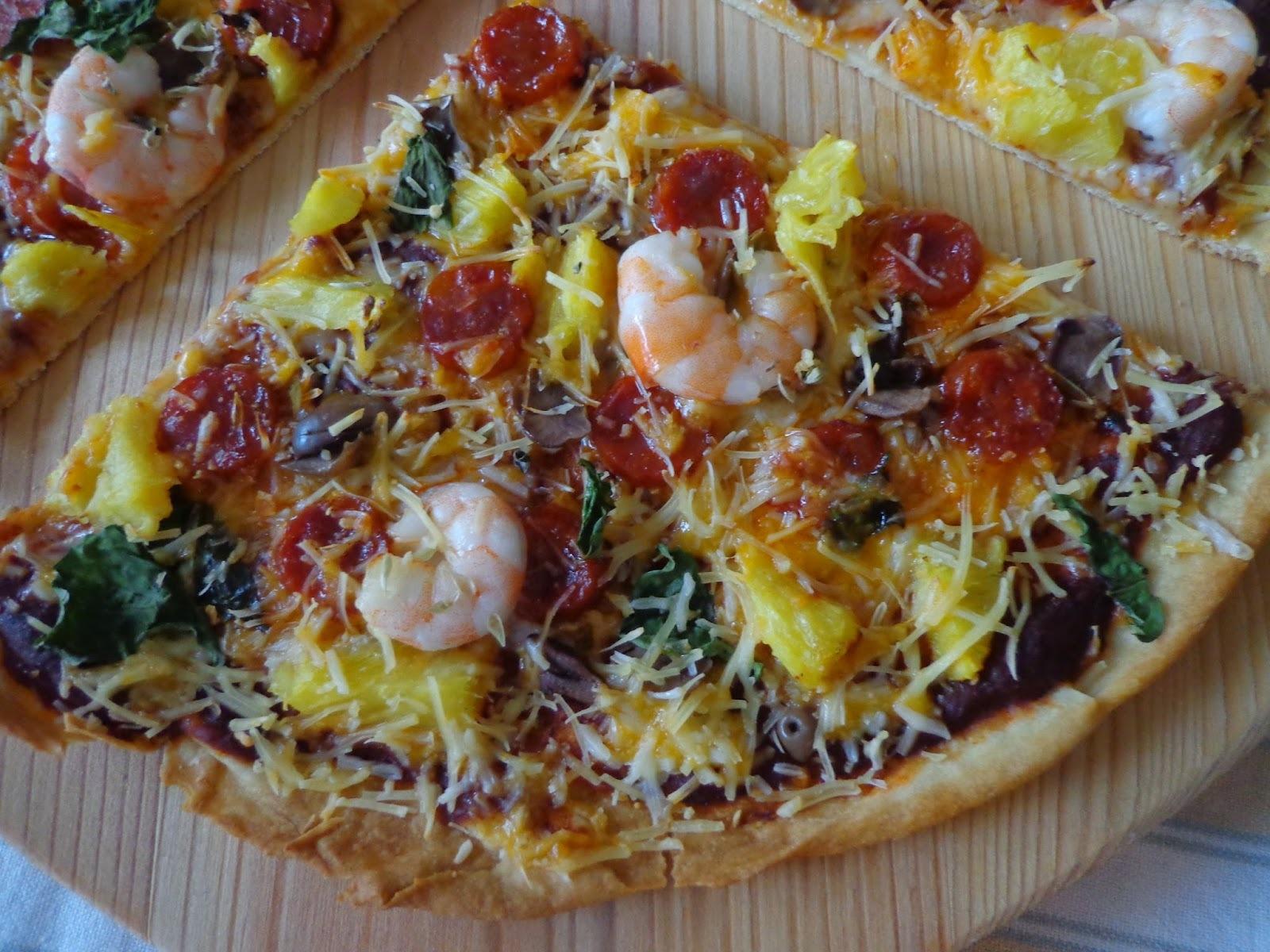 Pizza de camarão, linguiça, azeitonas e ananás aromatizada com manjericão