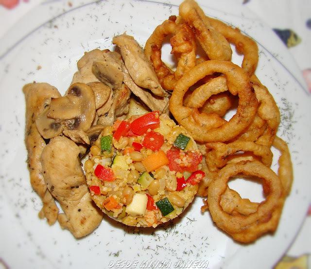 Iscas de peito de frango com mostarda e mel acompanhados com farofa de cuzcuz com feijão branco e legumes e anéis de cebolas.