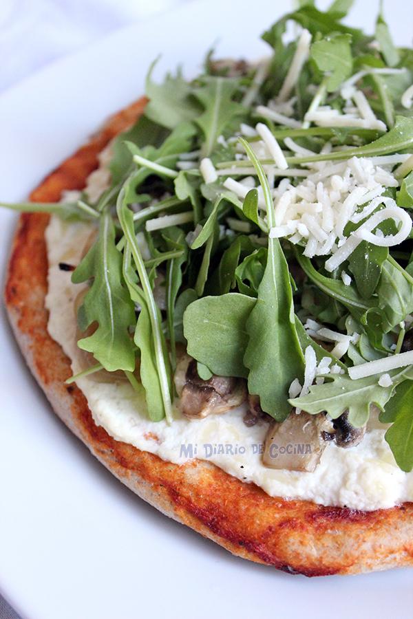 Pizza con ricotta, cebolla caramelizada, champiñones y rúcula