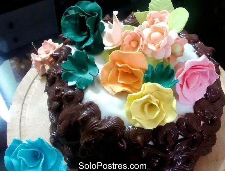 Torta de cumpleaños decorada con ganache y rosas de colores