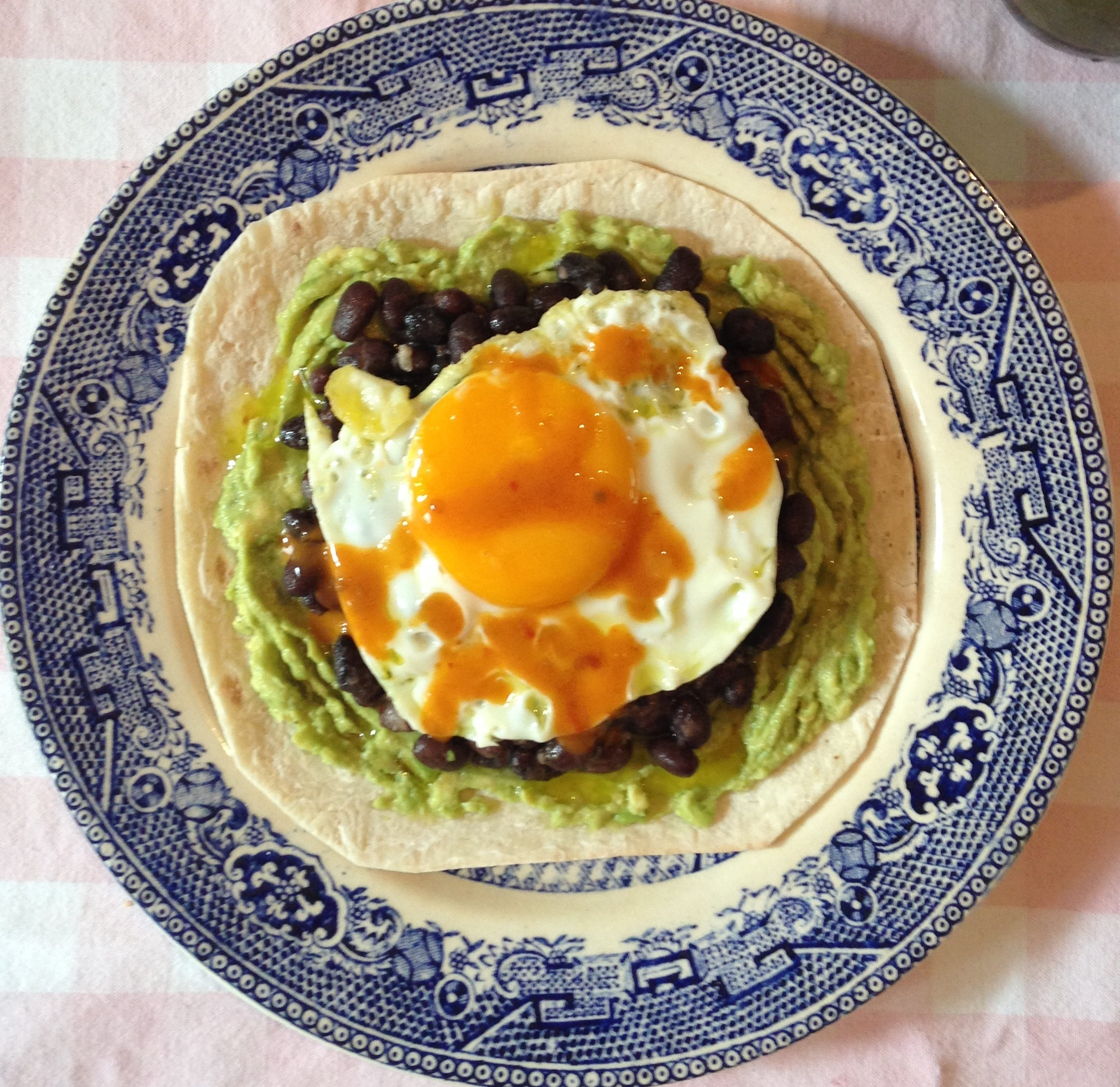 Amazing Breakfast Tortilla with crushed avocado, black beans and coconut oil fried egg (GF)