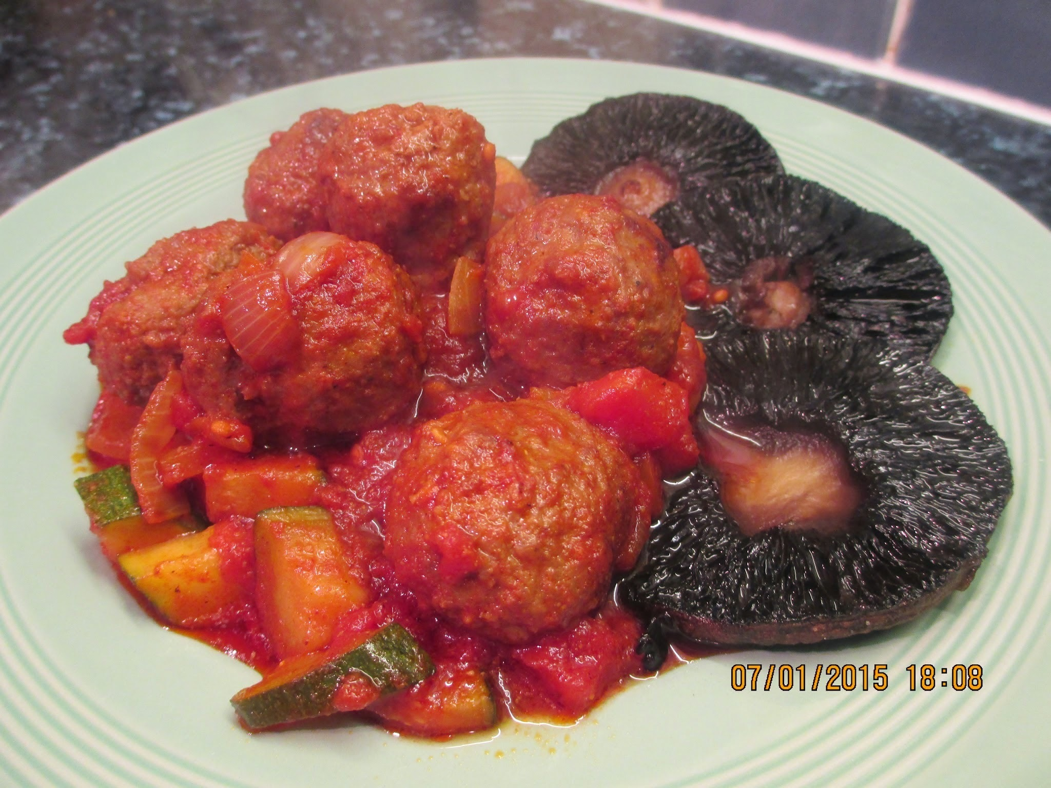 Meatballs in tomato sauce with grilled field mushrooms.