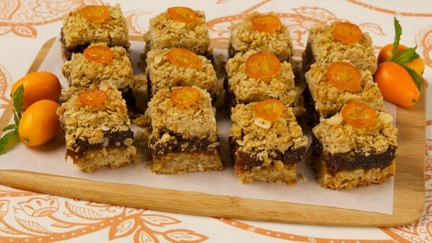 Orange Date Squares 	             rolled oats all-purpose flour packed brown sugar grated orange rind salt cold butter sliced hazelnuts pitted dates granulated sugar lemon juice orange juice