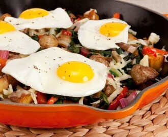 Potato and Chard Hash With Sunny-Side-Up Eggs 	             mini white potatoes olive oil small onion butter salt pepper cloves garlic sweet red pepper coarsely shredded Swiss chard shredded sharp white cheddar cheese eggs