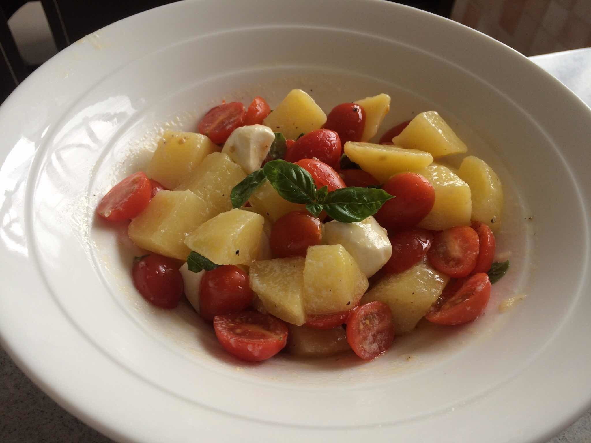 Potato salad with cherry tomatoes and mozzarella balls in buttermilk sauce