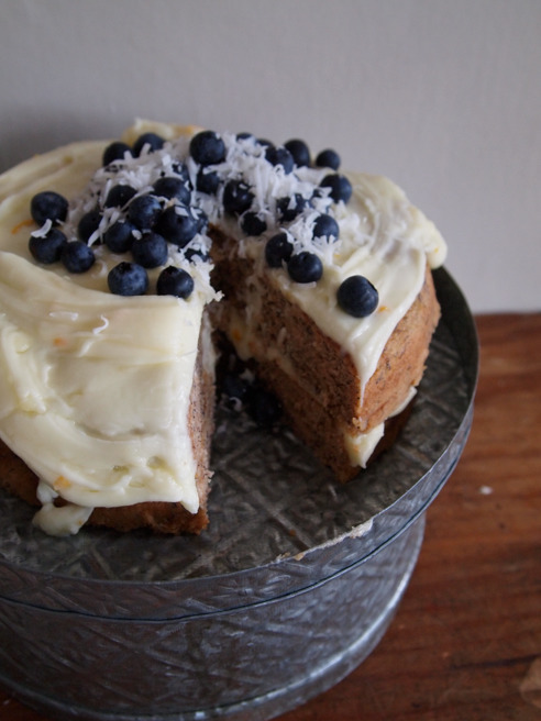 Banana cake with cream cheese frosting, blueberries and coconut. Gluten free