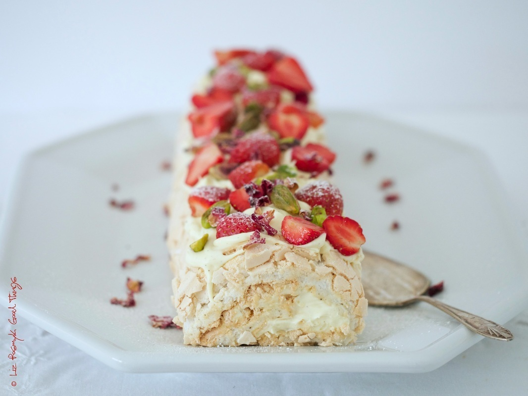 Meringue roulade with fresh berries, pistachios and rose petals