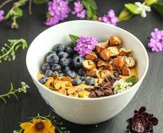 Peach smoothie bowl with fresh blueberries, pistachios, dark chocolate and pretzels