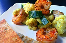Groene curry met bloemkool, courgette & scampi