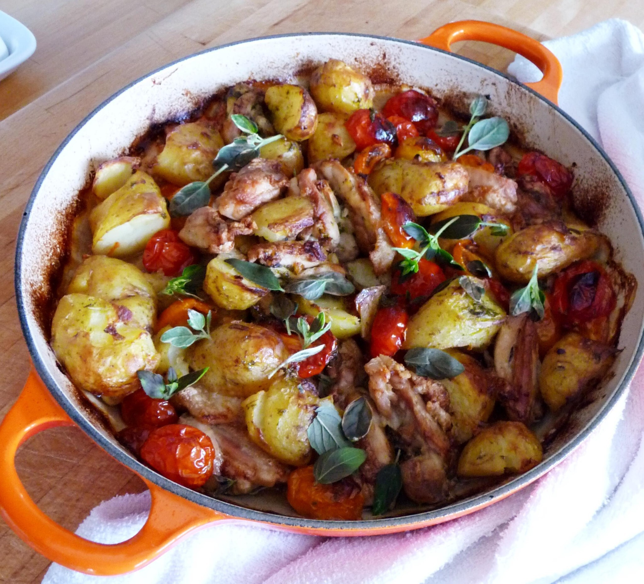 Crispy chicken thighs, roasted tomatoes and crushed new potatoes