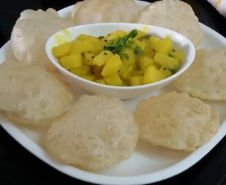 Luchi or Bengali Style Poori served with Aloo Chorchori or Potato Curry with Kalonji or Nigella seeds ( Kalojeera )