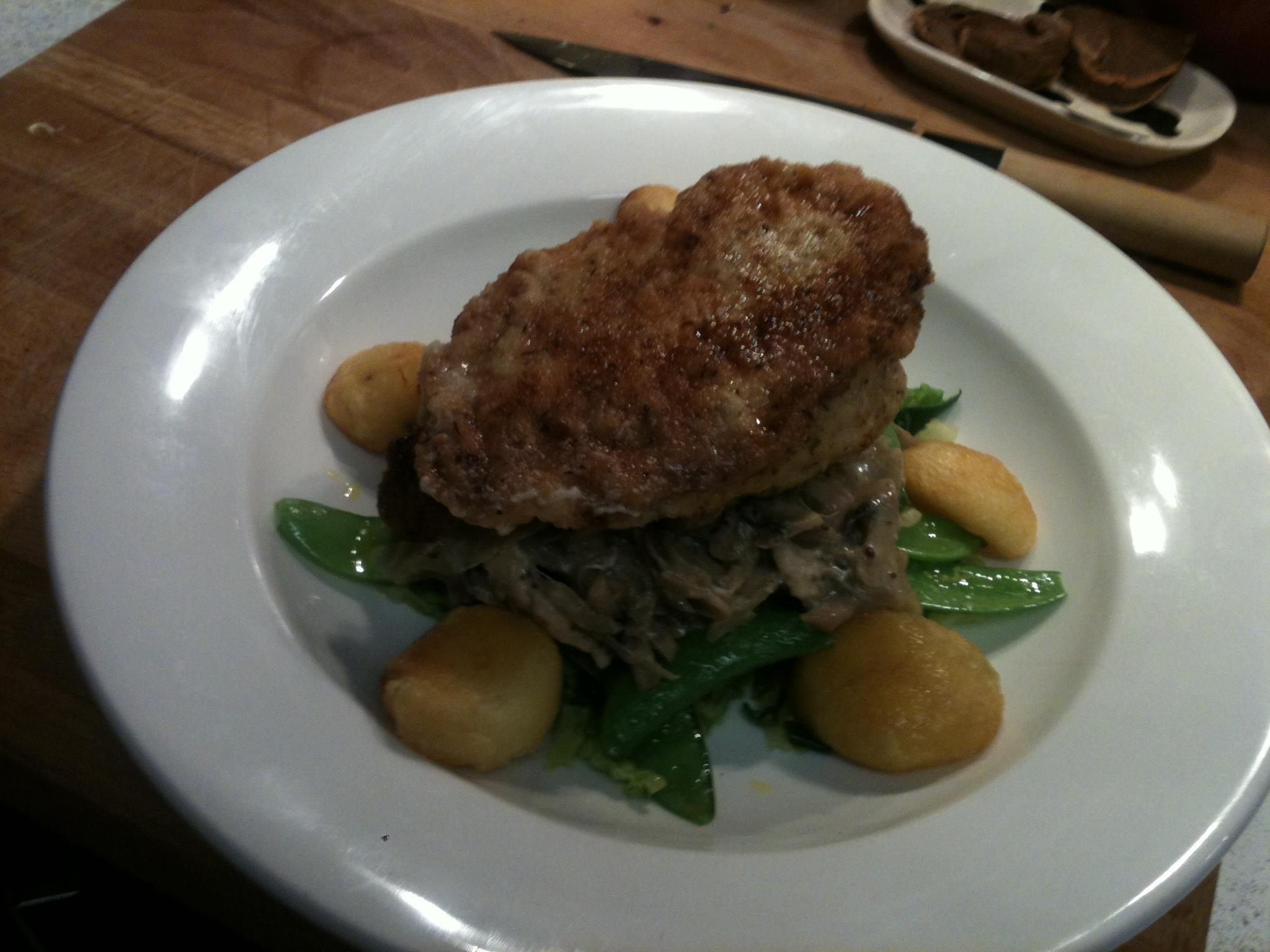 Garlic buttered chicken kiev with almond roast potatoes, mushroom fricasse & mangetout