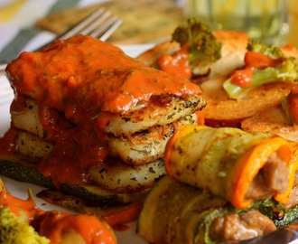 Basa Fish Fillet served in a bed of grilled zucchini and topped with red creamy sauce, some steamed veggies and garlic roasted bread