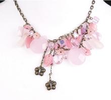halsketting met roze glaskralen en bronskleurige vlindertjes